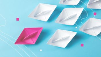 Image of white paper boats following a pink paper boat